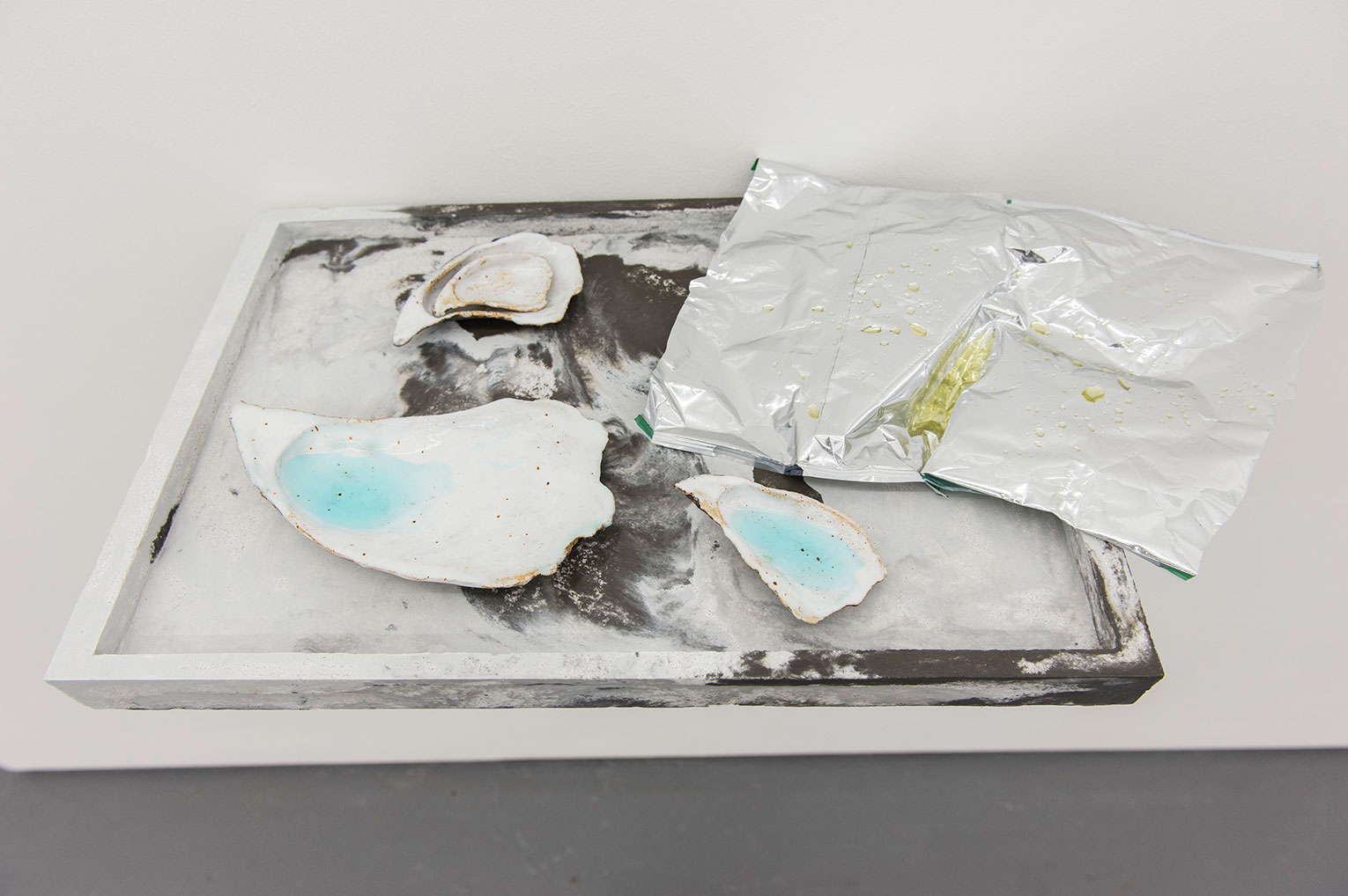 <b>Title:&nbsp;</b>Not Me But Me<br /><b>Year:&nbsp;</b>2016<br /><b>Medium:&nbsp;</b>Ciment Fondu, liquid soap, glazed ceramic, crisp packet, and resin<br /><b>Size:&nbsp;</b>8 x 57 x 31 cm