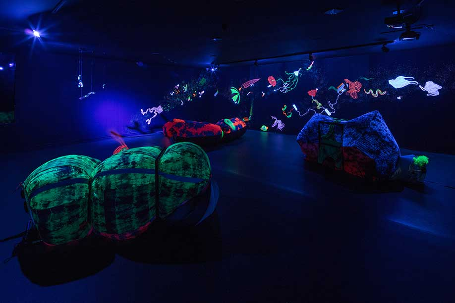 <b>Title: </b>Atrophic Chain, In collaboration with Attua Aparicio from Silo Studio<br /><b>Medium: </b>UV lights, Mouth blown Uranium glass, welded metal structures, tyed dyed ripstock inflatables, mural.<br /><b>Size: </b>Dimensions variable